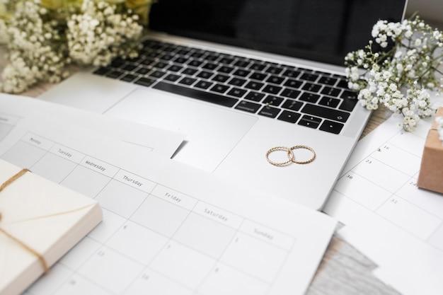 Close-up do calendário; alianças de casamento; flores de respiração do bebê e laptop na mesa Foto gratuita