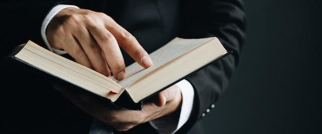 Close up do dedo do homem de leitura que aponta o texto no livro. Foto Premium