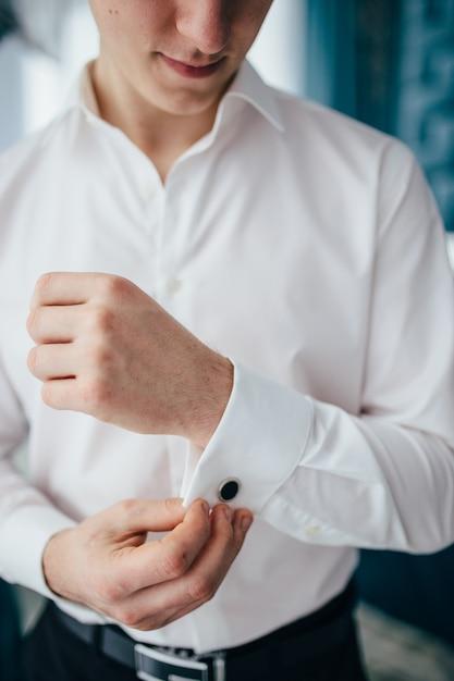 Close-up do homem de camisa, vestir-se e ajustando a gravata no pescoço em casa. Foto Premium