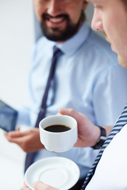 Close-up do homem de negócios com chávena de café Foto gratuita