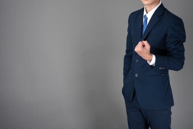 Close-up do homem de negócios de terno azul é bem sucedido em fundo cinza Foto Premium