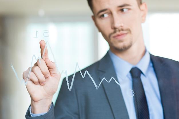 Close up do homem de negócios que aponta ao gráfico no vidro Foto gratuita