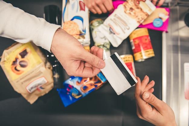 Close-up do homem que dá um cartão de crédito no balcão de caixa. Foto Premium