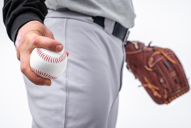 Close-up do homem segurando beisebol e luva Foto gratuita