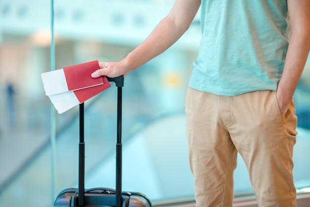 Close-up do homem segurando passaportes e cartão de embarque no aeroporto Foto Premium