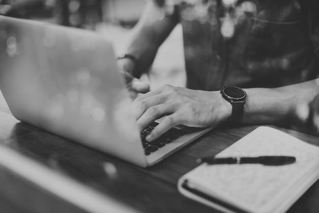 Close-up do homem usando laptop no café em tons de cinza Foto gratuita