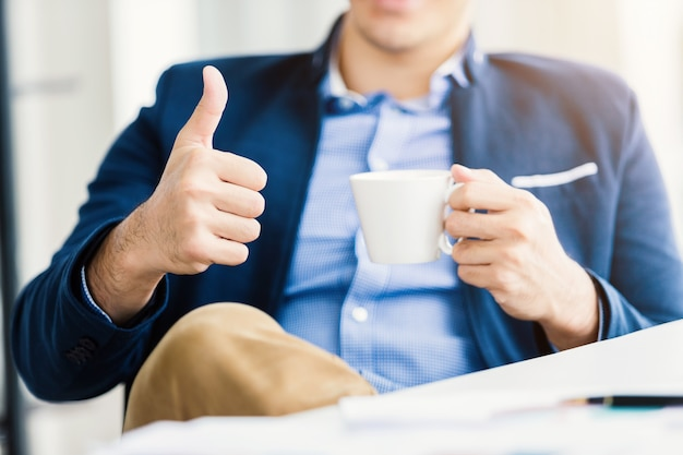 Close-up do jovem empresário de humor feliz, mostrando os polegares para cima trabalhando com segurando uma xícara de café, sentar-se à mesa Foto Premium