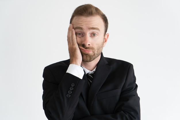 Close up do líder de negócio cansado e furado. barbudo jovem homem caucasiano na gravata e jaqueta Foto gratuita