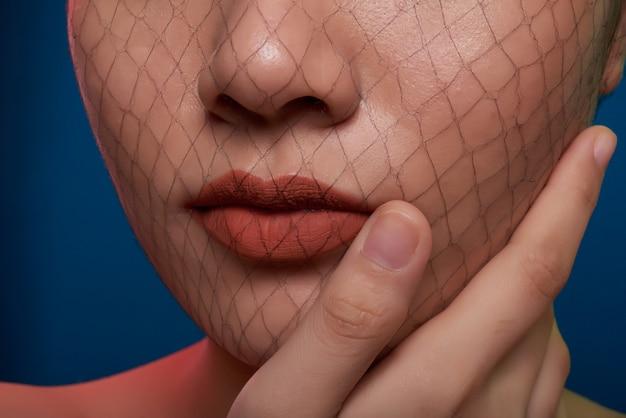 Close-up do nariz e boca de mulher irreconhecível, posando no estúdio com arrastão, cobrindo o rosto Foto gratuita