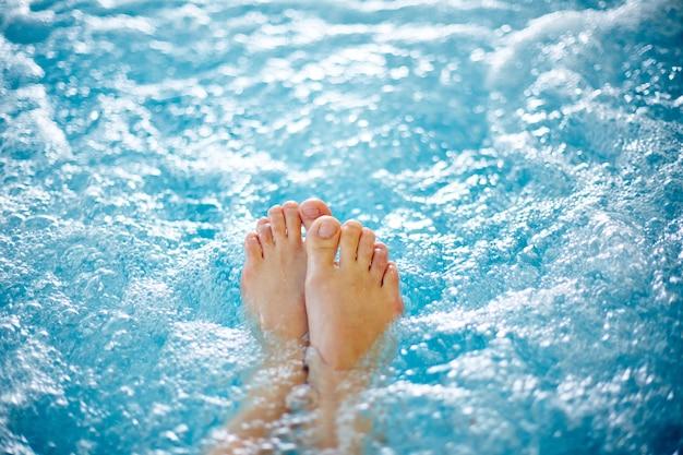 Close-up do pé feminino na banheira de hidromassagem Foto gratuita