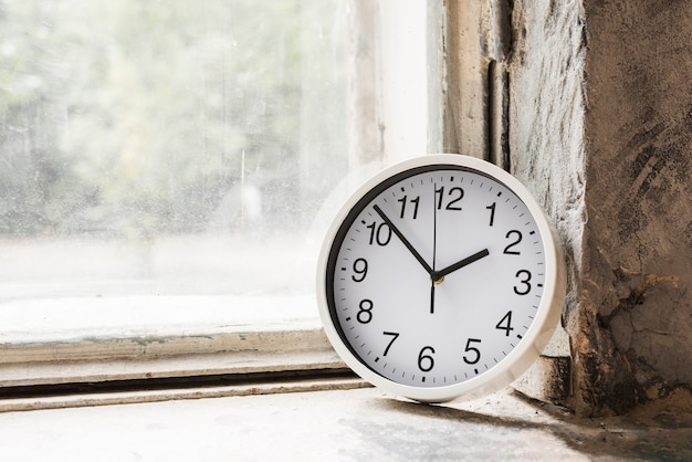 Close-up do pequeno relógio redondo branco perto da janela de vidro Foto gratuita