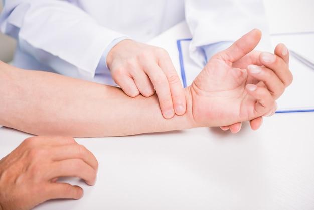 Close-up do pulso de medição do médico de seu paciente. Foto Premium