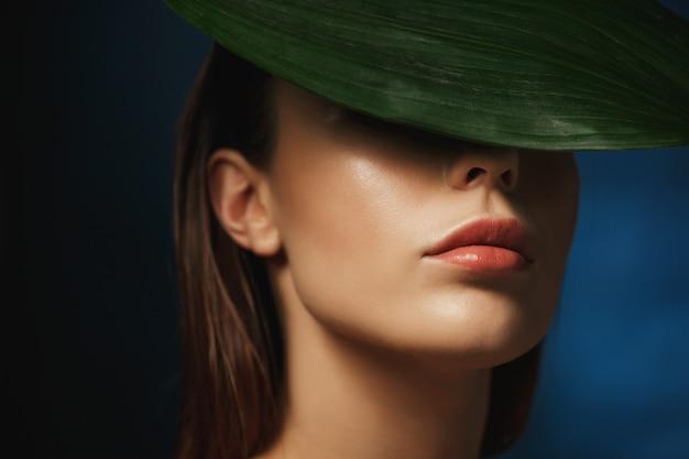Close up do rosto da coberta da jovem mulher atrás da folha verde fresca. Foto gratuita