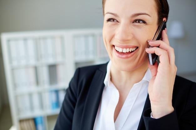Close-up do sorriso da mulher com o telefone móvel Foto gratuita