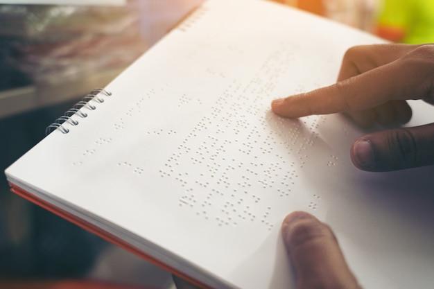 Close-up dos dedos lendo braille, mão de uma pessoa cega lendo algum texto em braille de um livro em braille. Foto Premium