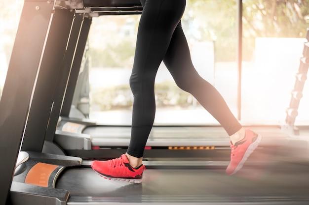Close-up dos pés de pernas musculosas da mulher correndo no treino de esteira no ginásio de fitness Foto Premium