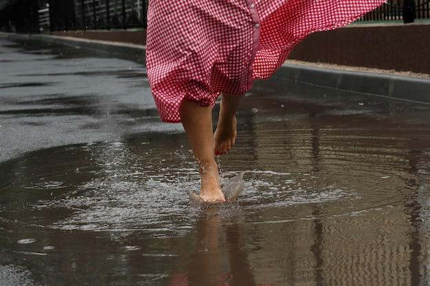 Close-up dos pés de uma menina que dançam em uma poça após uma chuva do verão. Foto Premium