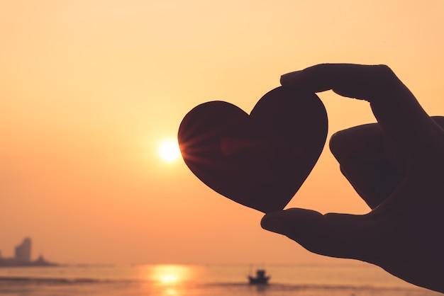 Close-up e silhueta de mão segurando coração vermelho durante o fundo por do sol Foto Premium