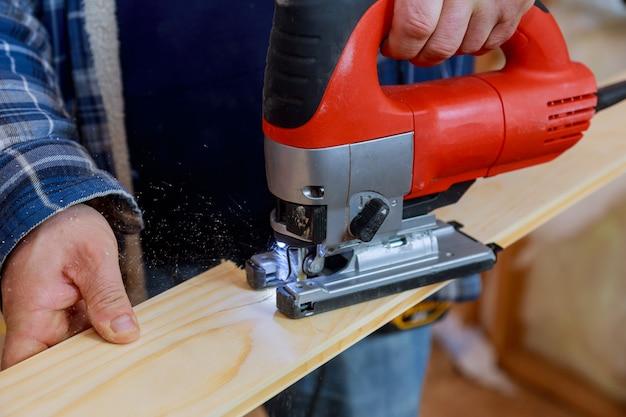 Close-up elétrico quebra-cabeça cortando um pedaço de madeira Foto Premium