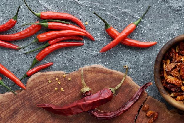 Close-up em red hot chilli peppers, fresco e seco, em madeira e pedra cinza Foto Premium