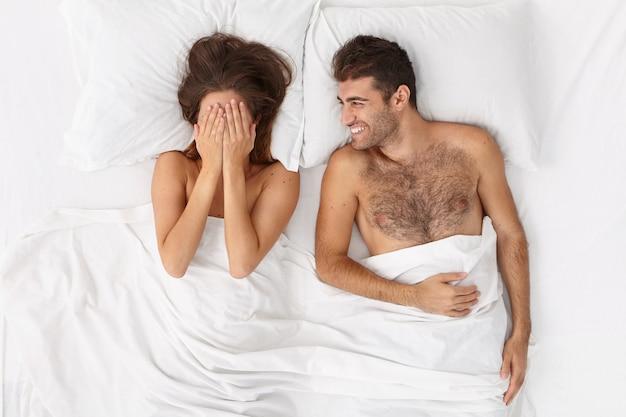 Close-up em um casal deitado na cama sob um cobertor branco Foto gratuita
