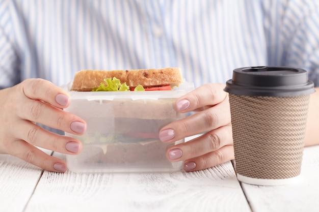 Close-up em um par de mãos femininas, removendo um sanduíche saudável saudável presunto pão integral de sua lancheira durante o almoço Foto Premium