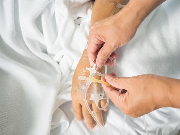 Close-up enfermeira mão ajustar três vias de iv conjunto para gotejamento intravenoso de gota salina fluida em branco Foto Premium