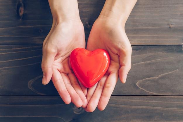 Close-up femininas mãos dando coração vermelho em fundo de madeira Foto Premium