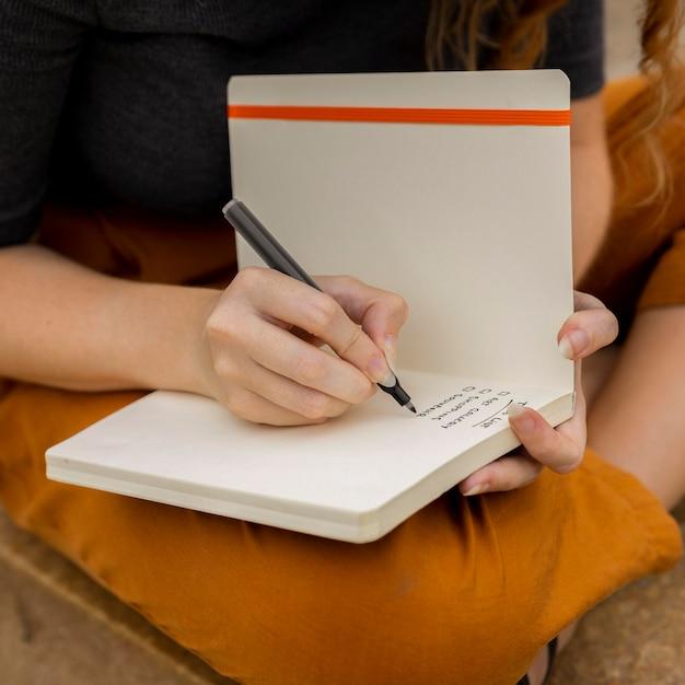 Close-up feminino escrevendo no diário Foto gratuita