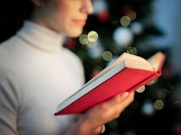 Close-up feminino lendo livro de histórias de natal Foto gratuita