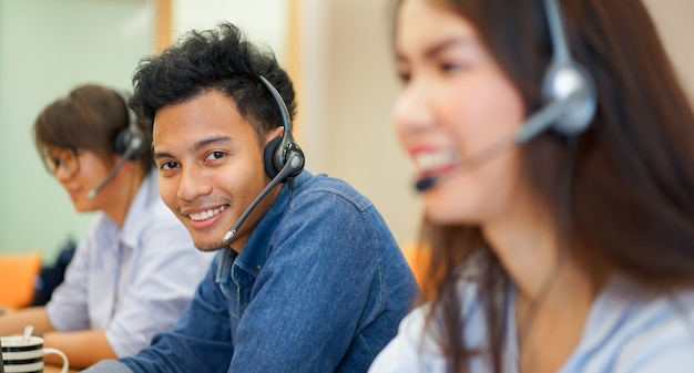 Close-up foco no homem asiático de call center com o trabalho da equipe Foto Premium