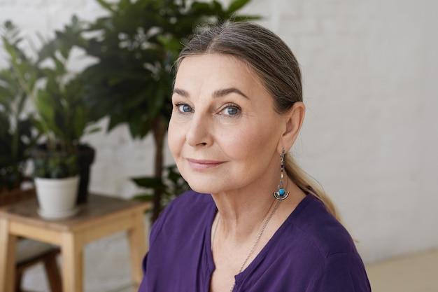 Close-up foto da encantadora senhora idosa caucasiana com olhos azuis, cabelos grisalhos reunidos e rugas posando dentro de casa Foto gratuita