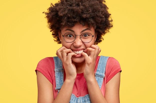 Close-up foto de desesperada irritada furiosa mulher afro-americana morde as unhas, tem uma expressão irritada e nervosa, reage a notícias negativas, vestida casualmente, isolada sobre uma parede amarela Foto gratuita
