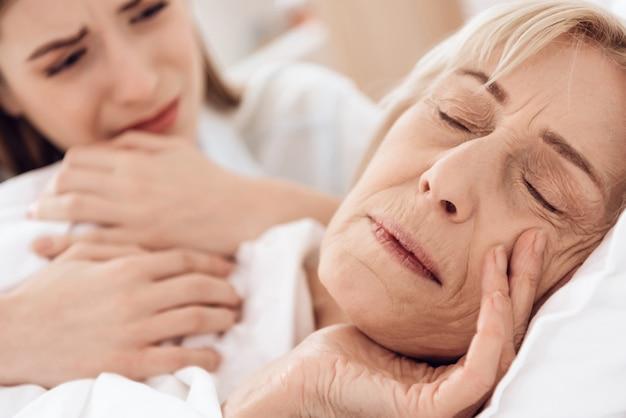 Close-up garota está cuidando da mulher idosa na cama em casa. Foto Premium
