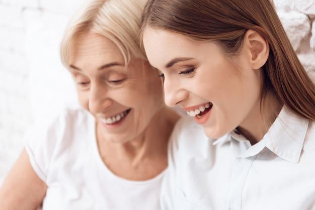 Close-up garota está cuidando de mulher idosa sorriem juntos Foto Premium