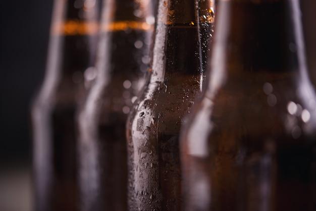 Close up garrafas de vidro de cerveja com gelo no fundo escuro Foto gratuita
