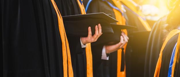 Close-up graduate segurando um chapéu. educação de sucesso de conceito na universidade Foto Premium