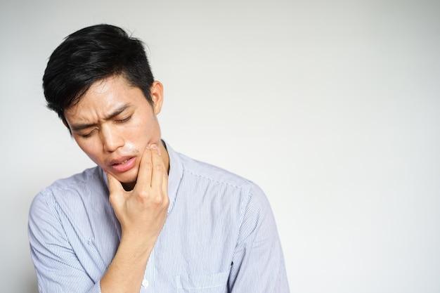 Close-up homem asiático sentindo dor de dor de dente Foto Premium