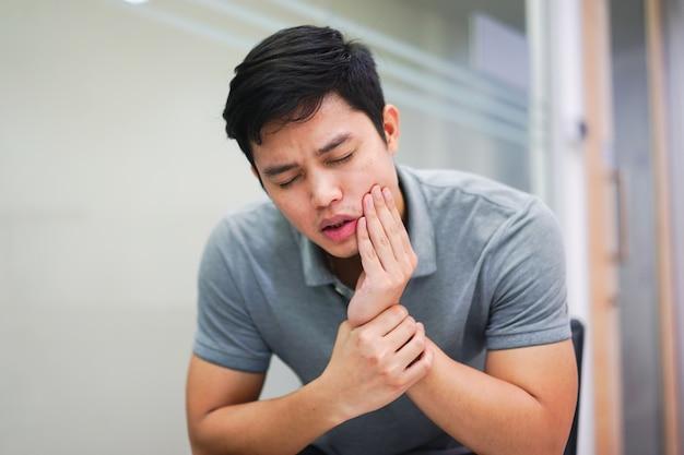 Close-up homem asiático sentir dor de dor de dente, conceito dental Foto Premium