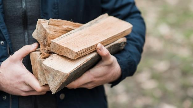 Close-up homem carregando madeira Foto gratuita
