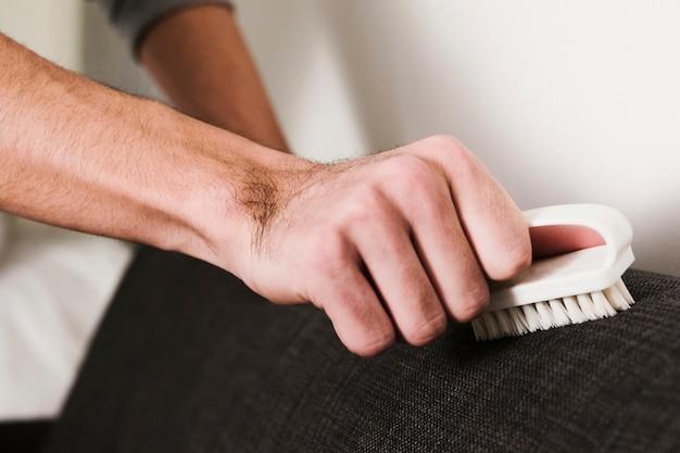 Close-up homem escovando o sofá Foto gratuita