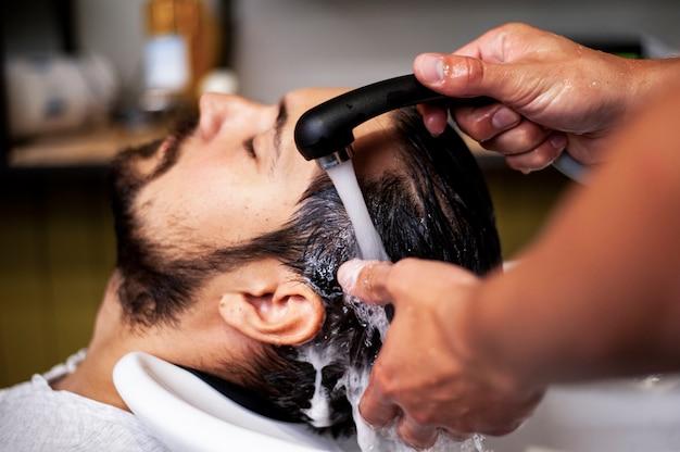 Close-up, homem, obtendo, cabelo, lave Foto gratuita