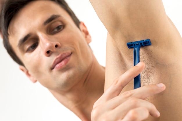 Close-up homem raspar sua axila Foto gratuita