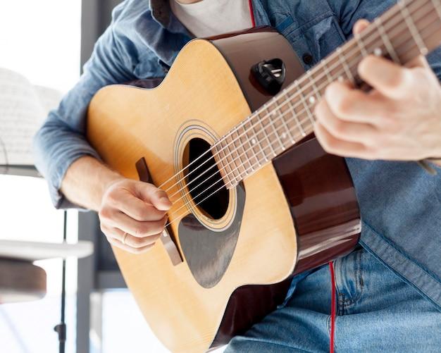 Close-up homem segurando um violão Foto gratuita