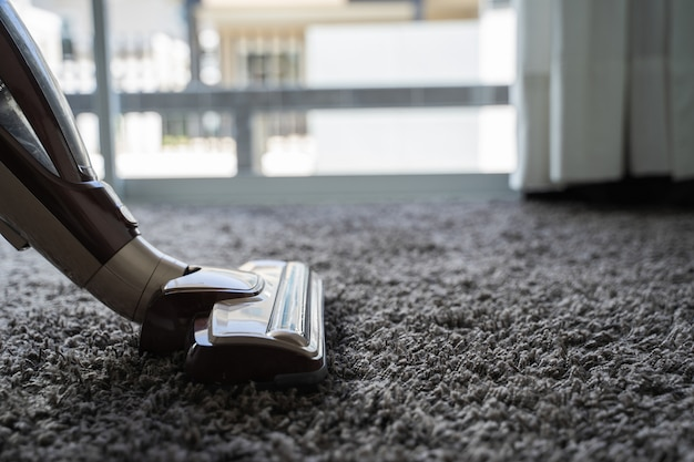 Close-up, homem, usando, um, aspirador de pó, enquanto, limpeza, em, a, sala Foto Premium