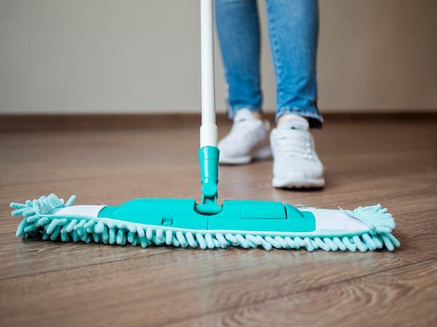 Close-up individual limpando o chão Foto gratuita