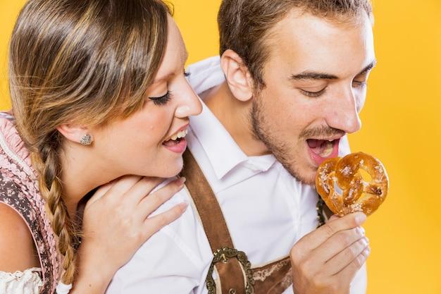 Close-up jovem casal comendo um pretzel Foto gratuita