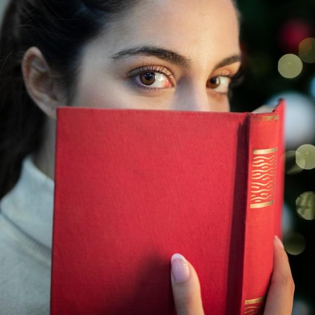 Close-up jovem cobrindo o rosto com o livro Foto gratuita