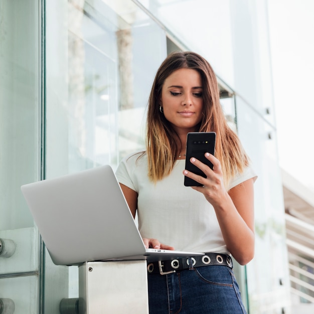 Close-up jovem com dispositivos portáteis Foto gratuita