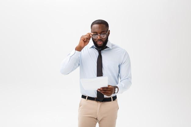 Close-up jovem empresário africano-americano com olhar para a câmera, mantendo o documento de papel Foto Premium